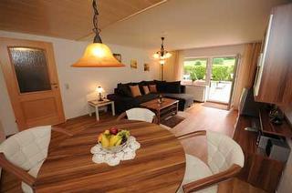 Wohnzimmer mit Essecke und direktem Zugang zum Garten