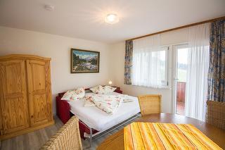 Wohnzimmer mit ausziehbaren Sofa und zugang zum Balkon