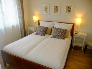 Doppelbett mit Nachttischen und -Lampen und großem Schrank