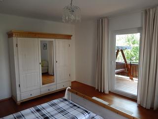 Schlafzimmer mit Kleiderschrank und Balkon