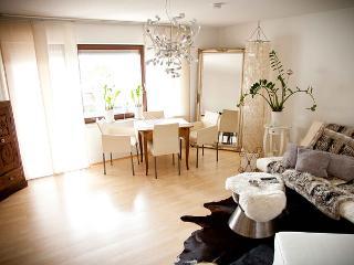 Lichtdurchflutetes und stilvolles Wohnzimmer mit Schlafcouch und Essgruppe