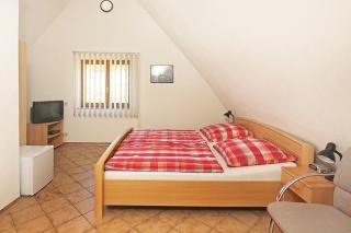 Das DZ zum Schloßberg ist mit Tisch, 2 Stühlen, 1 Mini-Bar, TV-Gerät, Radiowecker und Ventilator sowie Ofen eingerichtet.
