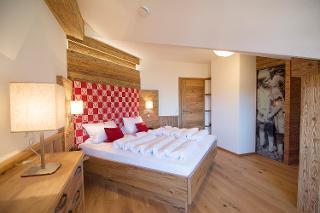 Alpenländischer Luxus im Stadl-Stil mit Massivholzbett und begehbarem Kleiderschrank. Hier lässt es sich herrlich träumen!