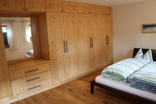 Schlafzimmer mit großzügigem Einbauschrank in Fichte massiv und großem integrierten Spiegel