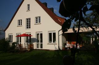 Sicht aus dem Garten auf das Haus kleiner Terrasse und Loggia / Urheber: Andreas Kenk / Rechteinhaber: © Andreas Kenk, Landhaus Köster & Kenk GbR